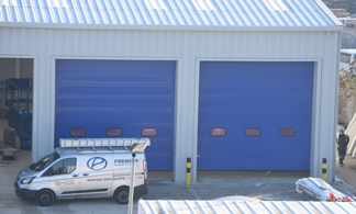 Grey cladding around 2 large industrial blue doors